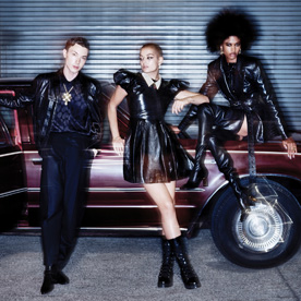Three people posing beside a car in leather clothes
